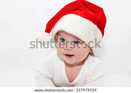 6 month old child wearing Santa's hat for Christmas