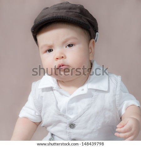 5 month old cute Asian baby boy dressed up, wearing a hat and making funny faces. Part of a series of square format images with different expressions - stock photo