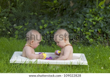 8 month old identical baby twin sisters having a bath in the garden. - stock photo