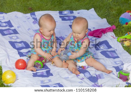 8 month old identical baby twin sisters having fun in the garden, playing with toys and a bottle of water. - stock photo