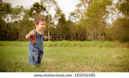 18 month old mixed race asian caucasian boy learning to walk outside in a grassy park on a cool autumn day - stock photo