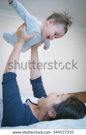 6 month old newborn mixed race Asian Caucasian boy plays happily with his Asian mother on a bed. Natural indoor lighting.