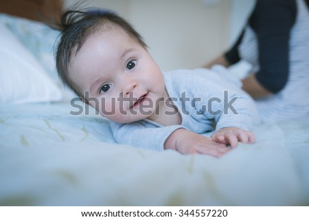 6 month old newborn mixed race Asian Caucasian boy plays on a bed with mother sitting in background. Natural indoor lighting. Cool tones - stock photo