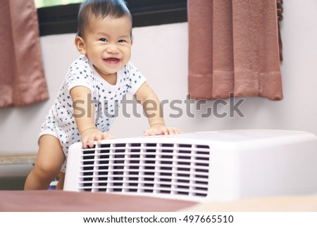 9 months Asian baby curious looking at mobile air conditioner