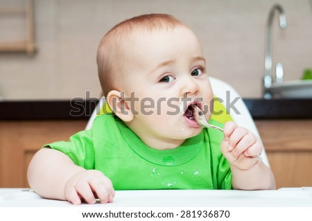 7 months baby eating cottage cheese with a spoon