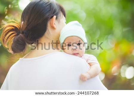 3 months baby with her mother in the garden - stock photo