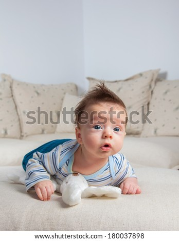 3 months old baby boy portrait at home laying on is tummy. - stock photo