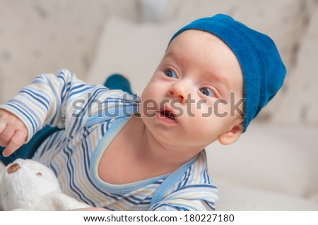 3 months old baby boy portrait at home trying to roll over. - stock photo