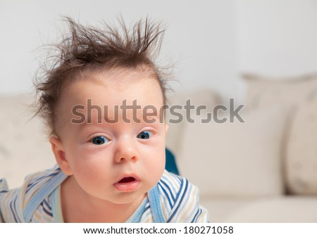3 months old baby boy portrait with messy hair and sleepy. - stock photo