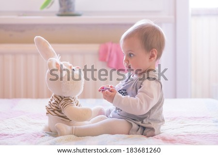 10 months old baby girl playing with plush rabbit - stock photo