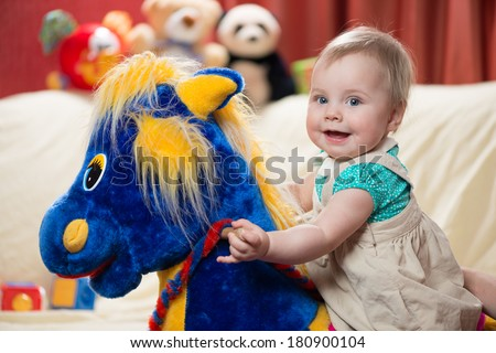 10 months old baby girl riding rocking horse - stock photo