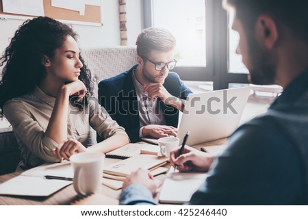 Morning brainstorm. Young handsome man in glasses using laptop while sitting at the office table with his coworkers - stock photo