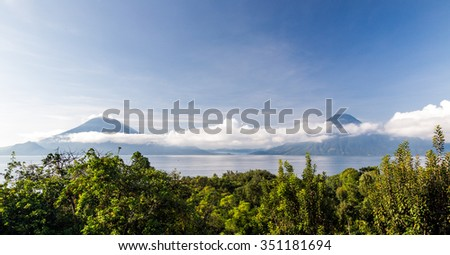 Morning view of calm Lake Atitlan, Guatemala, with two Volcanoes in the background.  - stock photo