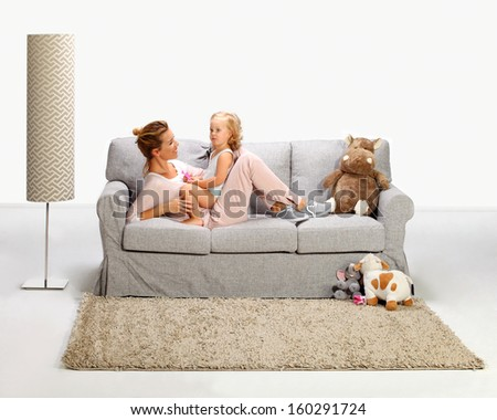 Mother and baby daughter playing on bad sofa 6 - stock photo