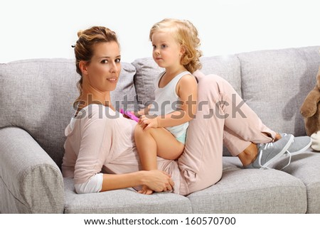 Mother and baby daughter playing on bad sofa 7 - stock photo