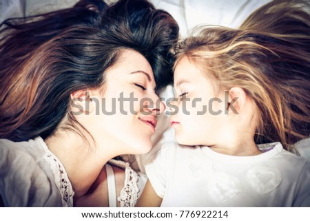 Mother and daughter embracing in bed asleep. Close up.