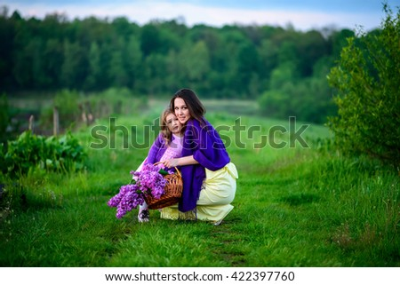 Mother and daughter enjoying sunset on a fabulous lake. Basket with a branch of lilac flower.  - stock photo