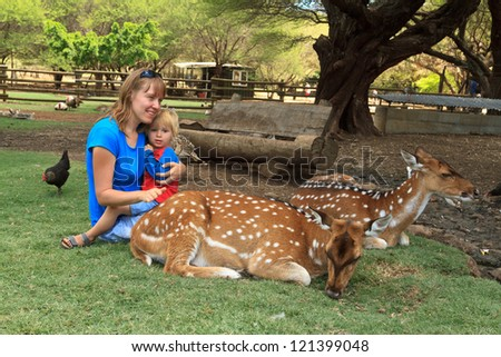 mother and son touching deers