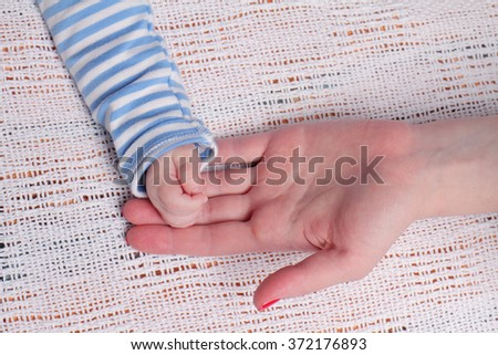 Mother holding baby's hand close up