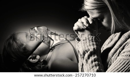 Mother prays for the health of seriously ill daughter.MANY OTHER PHOTOS FROM THIS SERIES IN MY PORTFOLIO.  - stock photo