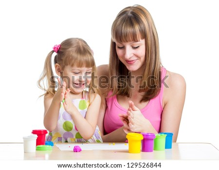mother teaching daughter to use colorful play dough - stock photo