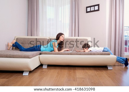 Mother using laptop on a sofa at home.Son with mobile phone on the floor.