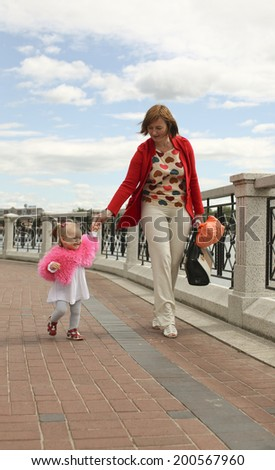 mother with her little daughter walking along the waterfront in the city
