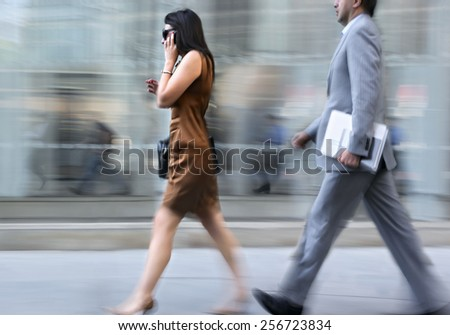 motion blurred business people walking on the street - stock photo