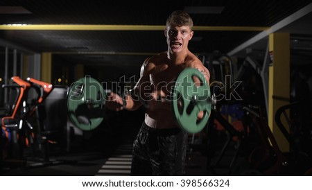 motivation Young adult bodybuilder doing weight lifting in gym. Muscular torso - stock photo