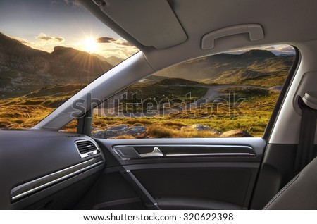 mountain sunset viewed from inside a car - stock photo