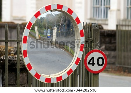 40 mph sign and road traffic safety mirror  - stock photo