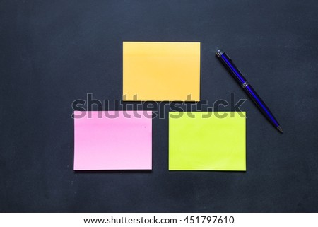 Multi color paper note and paper clip and pen on blackboard - stock photo