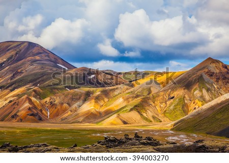 Multi-colored mountains from mineral rhyolite are lit with sun. Travel to Iceland in the July. Summer volcanic tundra