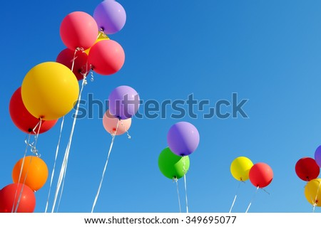 multicolored balloons  in the city festival on blue sky background