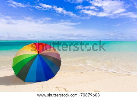 Multicolored umbrella on tropical beach with blue sky and cloudscape background. - stock photo
