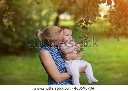Mum holds on hands of a small baby next to the bushes , the kid touches the foliage , autumn in the park in the summer on the nature