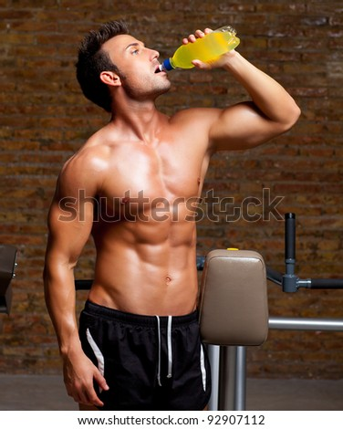 muscle shaped man at gym relaxed drinking energy drink