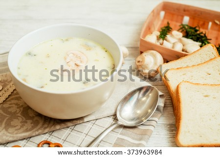 mushroom soup with potatoes , carrots , green and white toast on a wooden background