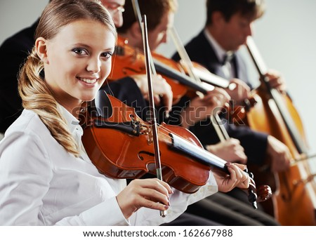 Musicians in concert, beautiful female violinist on foreground - stock photo