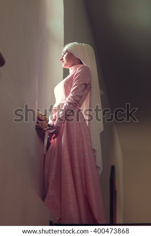 Muslim girl at the window in a pink dress