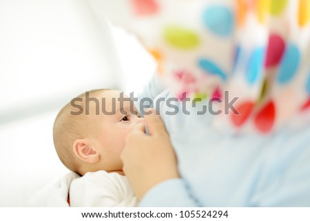 Muslim mother is breast-feeding her baby - stock photo