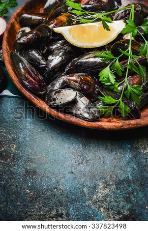 mussels with lemon and ingredients for cooking in wooden plate on rustic background, top view, place for text - stock photo