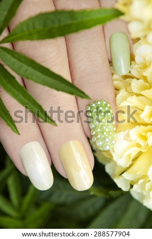 Nail design with pearl rhinestone and multi-colored mother of pearl lacquer on a woman's hand. - stock photo