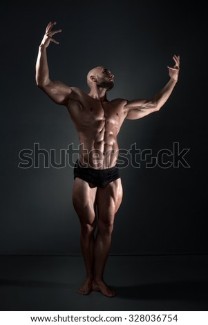 naked man posing in the studio on a dark background
