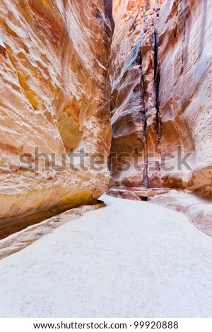 narrow way Siq and water channels to ancient city Petra, Jordan - stock photo