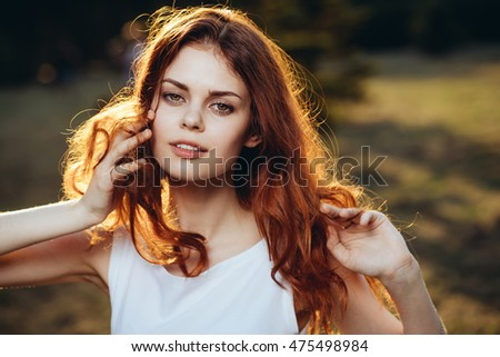 nature. Woman outdoors , hands in her hair , in the rays of the setting sun in the park