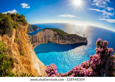 Navagio beach with shipwreck and flowers against sunset in Greece