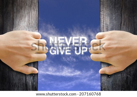 """Never Give up"" text in the sky behind 2 hands opening the wooden door. - stock photo"
