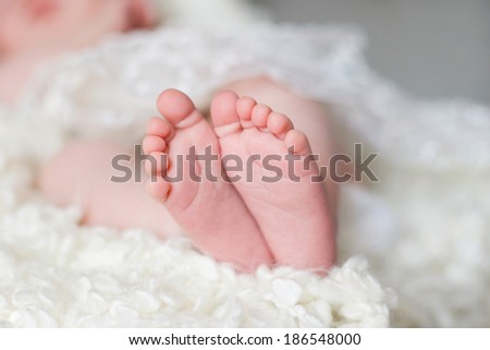 new born baby feet on a white blanket