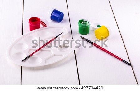new brushe and palette with cans of paint on white wooden background